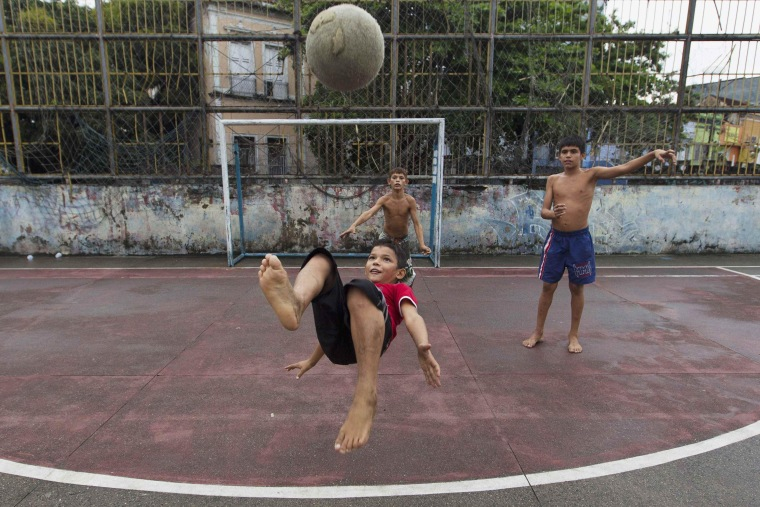 "Image: Boys play a Sunday ""pelada"" soccer match in the center of Manaus"