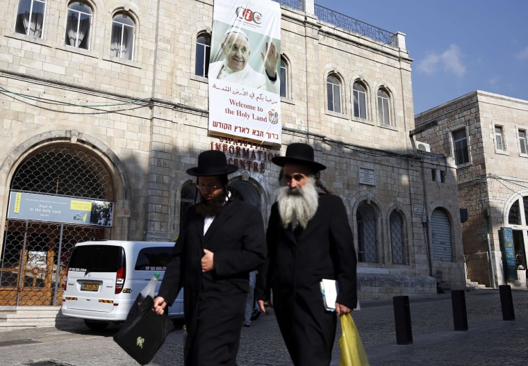 Image: Two Ultra Orthodox Jews walk past a large poster bearing the portrait of Pope Francis