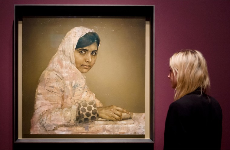 A gallery worker poses with a painted portrait of Malala Yousafzai, the teenage Pakistani advocate for girls education who was shot in the head by the Taliban in 2012, by Jonathan Yeo at the National Portrait Gallery in central London on Sept. 10, 2013.