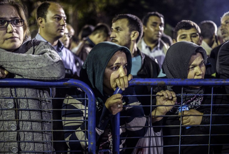 Image: People stand in front of a hospital as they wait for news of relatives