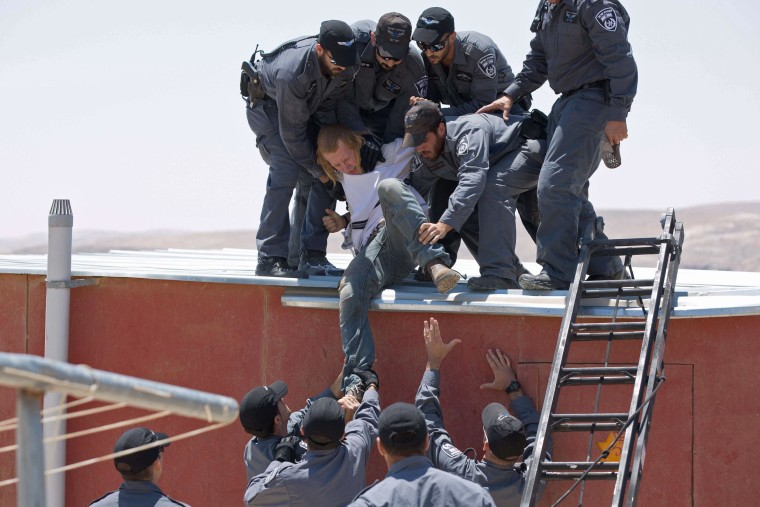Israeli police remove a settler from the top of a house in the illegal West Bank settlement of Maale Rehavam.
