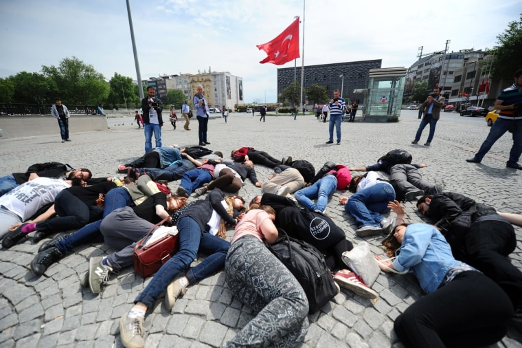Protesters lie down, acting as dead miners in front of a Turkish flag at half staff at Taksim Square on Wednesday 2014 in Istanbul.