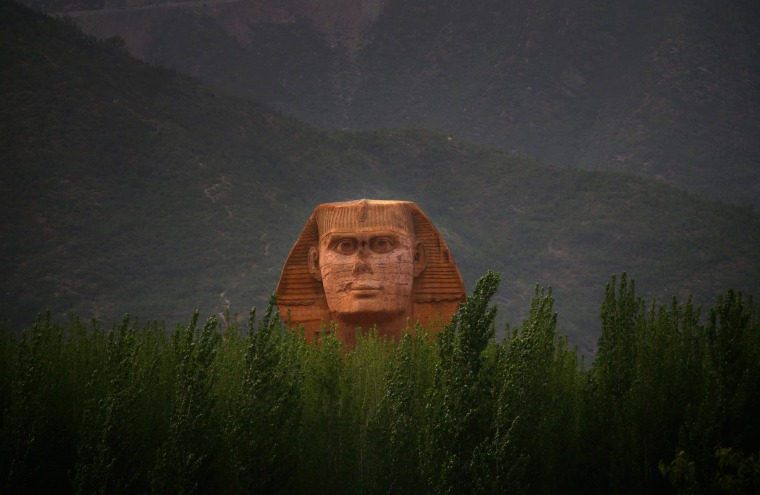 Image: The head of a full-scale replica of the Sphinx, which is part of an unfinished theme park that will also accommodate the production of movies, television shows and animation, is seen behind trees on the outskirts of Shijiazhuang