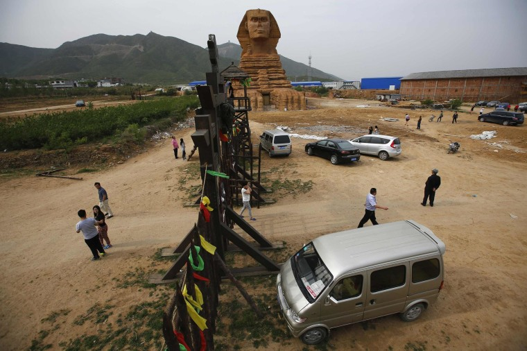 Image: People visit a full-scale replica of the Sphinx, which is part of an unfinished theme park that will also accommodate the production of movies, television shows and animation, on the outskirts of Shijiazhuang