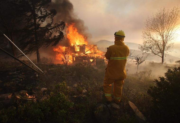 A firefighter keeps an eye on a burning house May 14, 2014 in San Marcos, California.