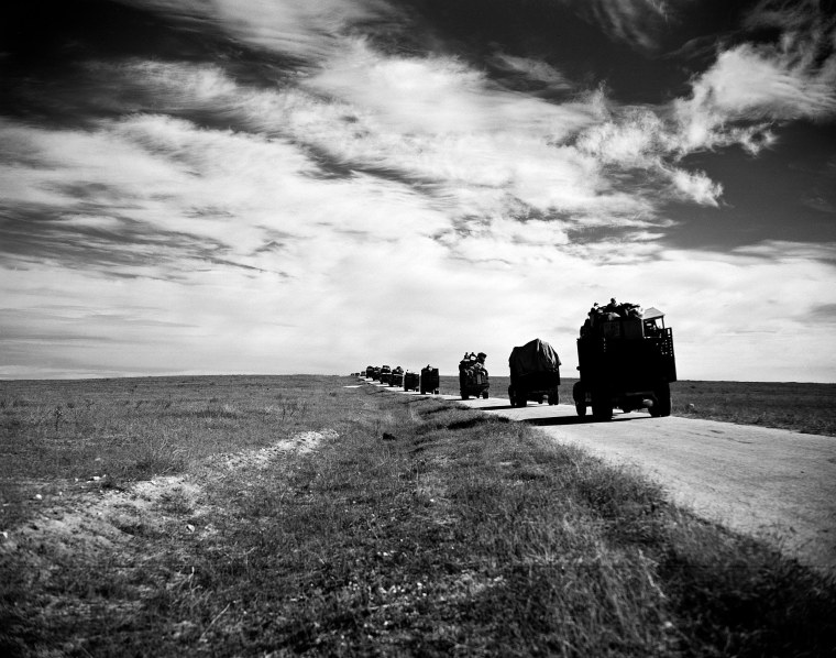 Image: A convoy of trucks and cars led by white U.N. jeeps travels through the Gaza desert carrying Arab refugees and their belongings from Gaza to Hebron.