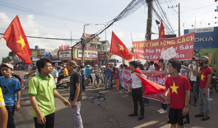 Workers wave Vietnamese national flags during a protest at an industrial zone in Binh Duong province May 14, 2014.