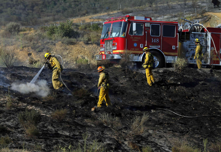 Image: A Los Angeles Country fire crew works on a hillside putting out hotspots on the Coco Fire in San Marcos California