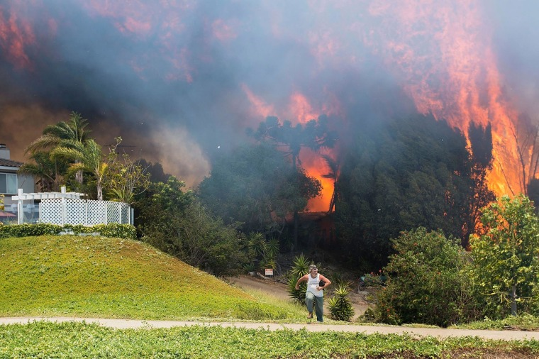 A man flees erupting flames as a house on Skimmer Court is engulfed by the Poinsettia Fire on May 14, 2014 in Carlsbad, California. Thirty homes have burned in the fast-moving Carlsbad blaze, fueled by record heat, high winds and dry conditions. At least four other fires advanced in nearby communities.  (Photo by Daniel Knighton/Getty Images) *** BESTPIX ***