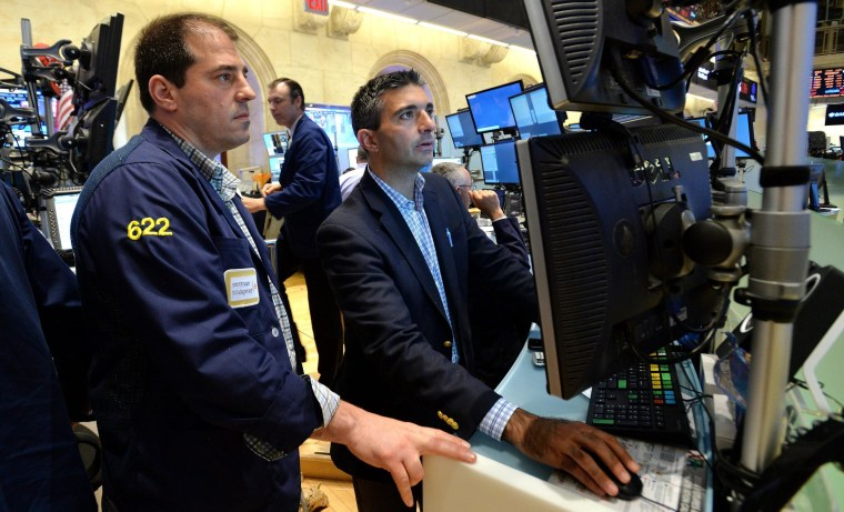 Traders work at the New York Stock Exchange on Thursday where the Dow fell over 1 percent on a handful of negative economic reports.