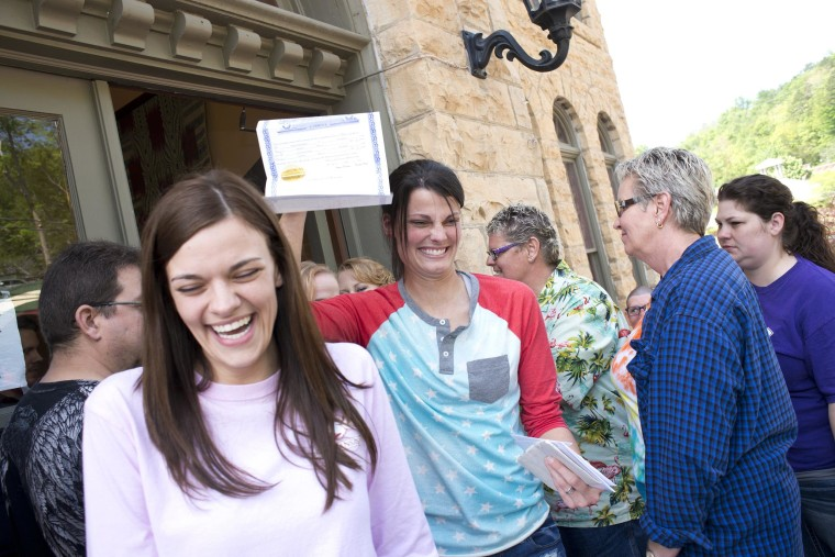 Image: Kristin Seaton holds up her marriage license as she leaves the courthouse in Eureka Springs, Ark., with her partner, Jennifer Rambo.
