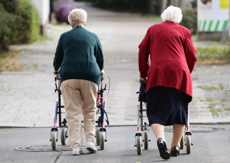Image: Two elderly women push shopping carts down a street