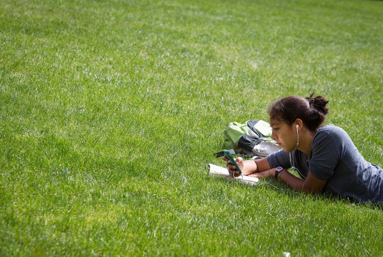 Image: A woman lies in the grass reading a book and listening to music