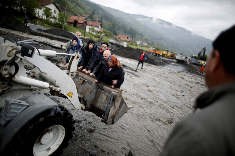 Image: People are carried by a front loader as they evacuate from their flooded houses in Topcic Polje