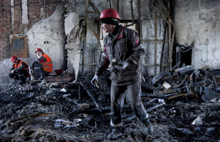 Image: Workers of the Ukrainian company Metinvest clear away debris in a government building in the eastern Ukrainian city of Mariupol