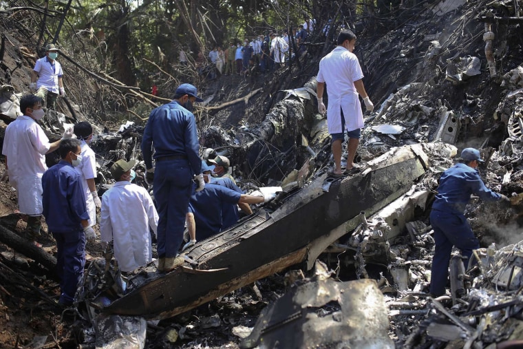 Image: Rescue workers search an air force plane crash site near Nadee village, in Xiang Khouang province