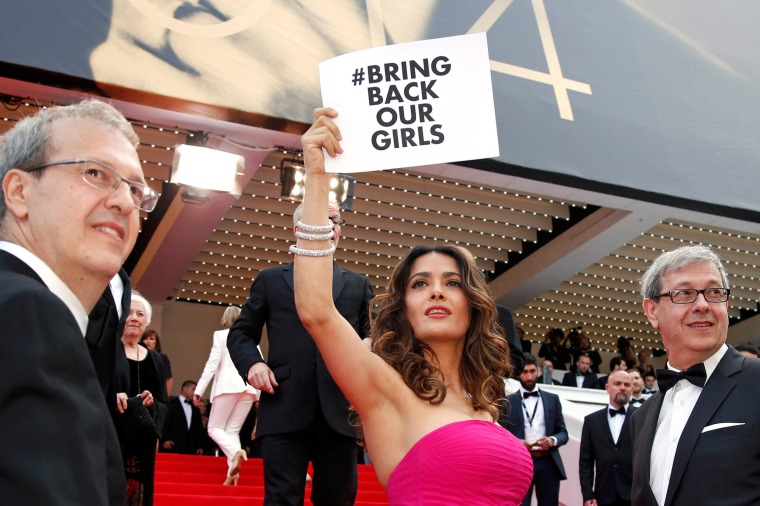 Image: Actress Salma Hayek holds a placard which reads 'Bring back our girls'at the 67th Cannes Film Festival in Cannes