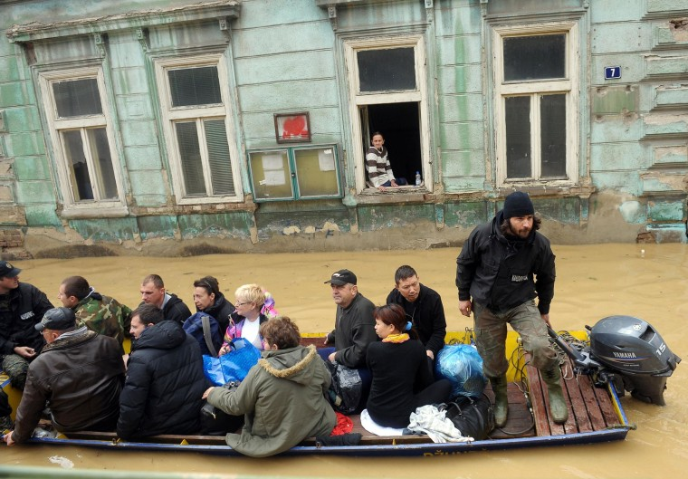 Image: A group is evacuated by boat over flooded streets in the town of Obrenovac