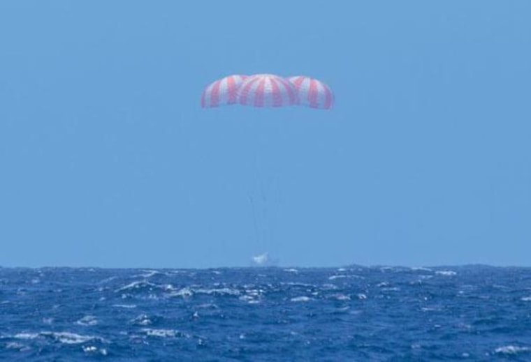A photo taken from a recovery ship shows SpaceX's Dragon cargo capsule splashing down in the Pacific with three parachutes floating above.