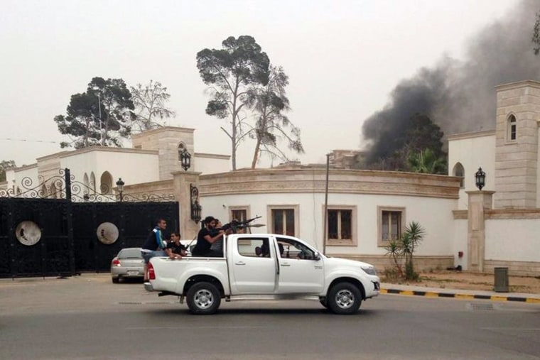 Image: Armed men aim their weapons from a vehicle as smoke rises in the background near the General National Congress in Tripoli