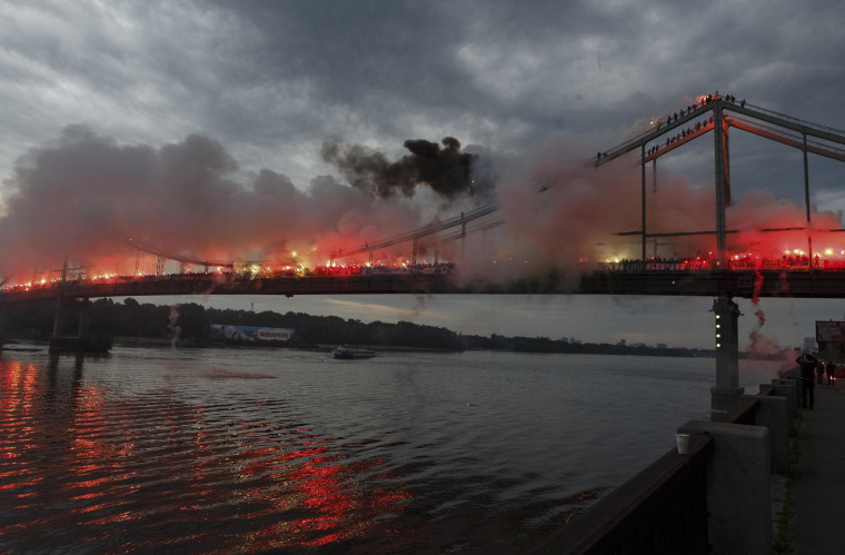 Image: Ukrainian soccer fans light flares on a bridge across the Dnieper River in Kiev