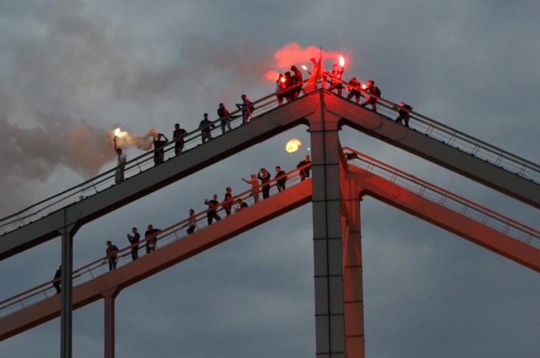 Image: Soccer fans burn torches on a bridge in Kiev, Ukraine