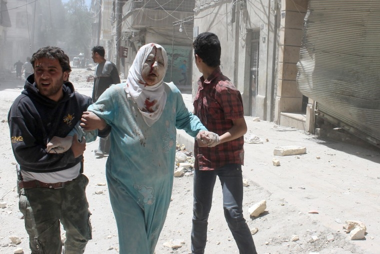 Image: Syrian residents help an injured woman following reported air strike