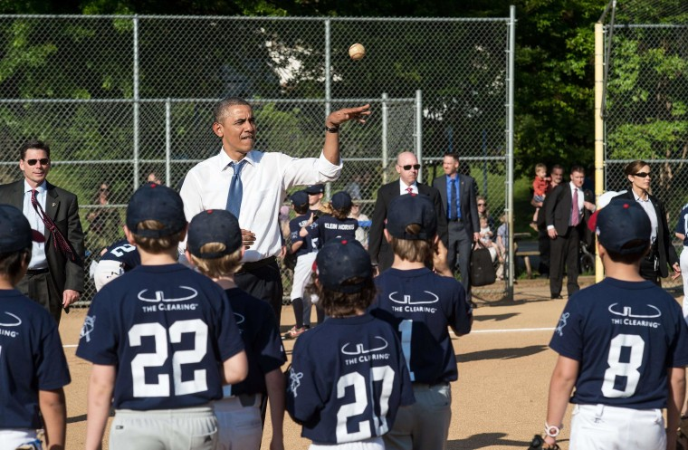 President Barack Obama tosses a ball to Little League baseball players as they warm up prior to games at Friendship Park in Washington on May 19, 2014.