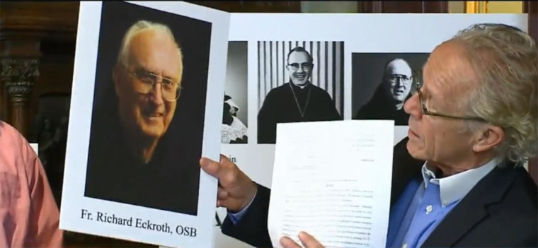 Image: A lawyer holds up a photo of Father Richard Eckroth.