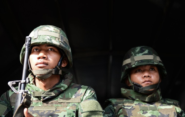 Image: Thai soldiers sit in an army truck outside the Government Public Relations Department