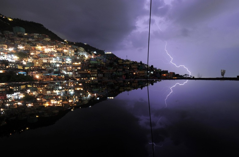 Image: A long exposure shows lightning in the sky with reflection in the water