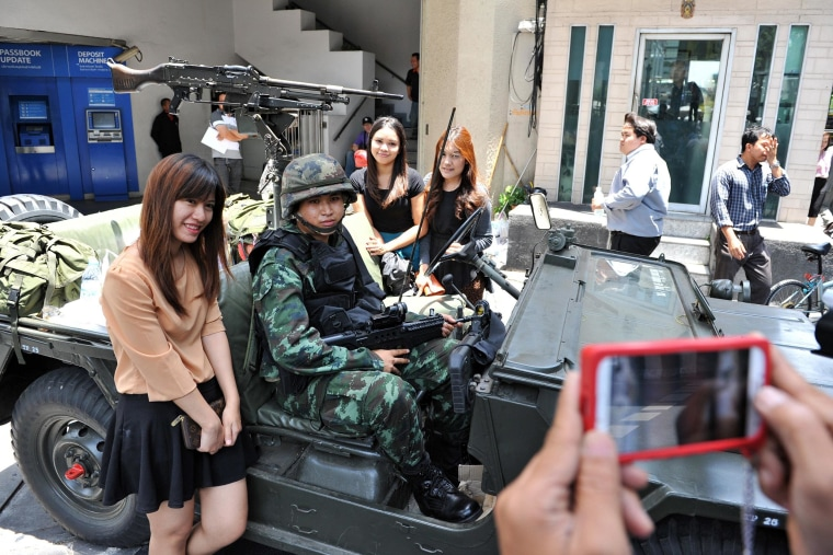 Image: Passersby pose for a photo with Thai army soldiers standing guard on a city center street after martial law was declared in Thailand