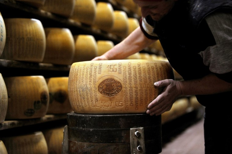 Image: A worker checks a wheel of seasoned Parmigiano Reggiano cheese in a factory in Italy