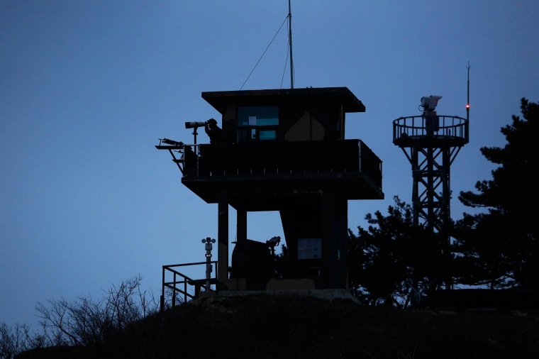 A South Korean soldier uses binoculars to look out to sea from a watchtower on the Yeonpyeong island, which lies just inside the South Korean side of the Northern Limit Line (NLL) in the Yellow Sea April 8, 2014. In 2010 North Korea fired multiple shells onto the island killing four people, including two civilians in a first such attack since the end of the 1950-53 Korean War. In subsequent years, the South Korean government has increased its military presence on the islands. Cliff tops are adorned with cruise missiles capable of striking Pyongyang, and the beaches are lined with barbed wire, soldiers, and mines. The two sides are still technically at war as the conflict ended in a mere truce, not a treaty. Picture taken April 8, 2014. REUTERS/Damir Sagolj (SOUTH KOREA - Tags: MILITARY SOCIETY POLITICS)