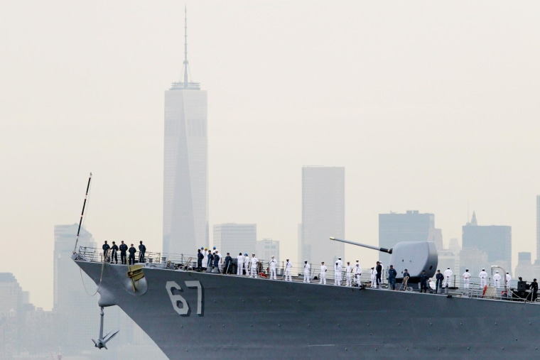 Image: Sailors line the bow of the destroyer USS Cole as it glides past One World Trade Center