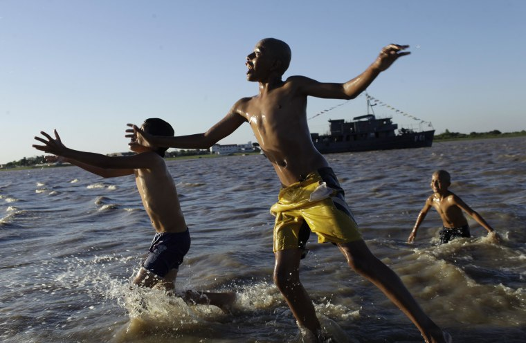 Children play in the water in Asuncion Bay, Paraguay, in 2012. A poll released Wednesday says Paraguay is the happiest country in the world.