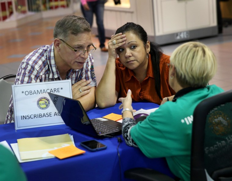 Angel Rivera and his wife Wilma Rivera sit with an insurance agent in Miami. An estimated 10 million Hispanics are newly eligible for health coverage under Obamacare.
