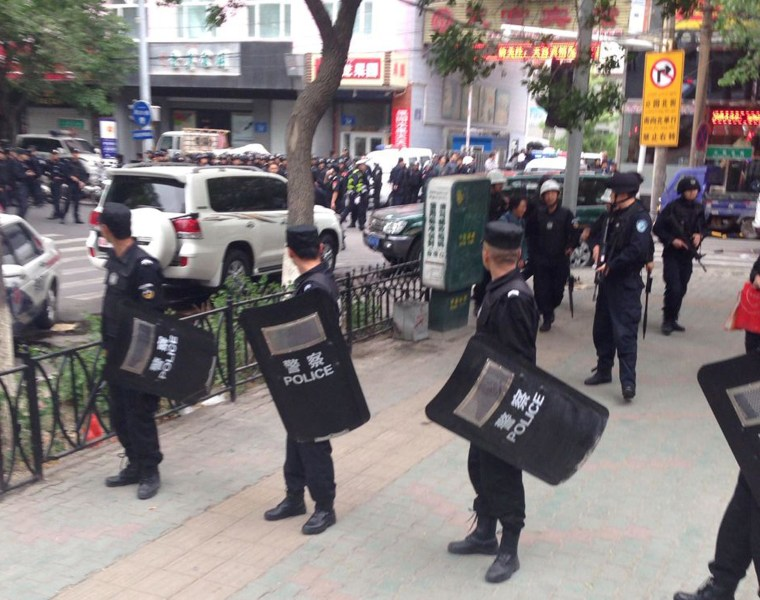 Image: Police officers stand guard near a blast site which has been cordoned off, in downtown Urumqi, capital of northwest China's Xinjiang Uygur Autonomous Region