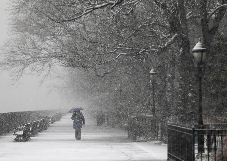 Image: A person walks on a deserted pedestrian walkway on a snowy morning in New York