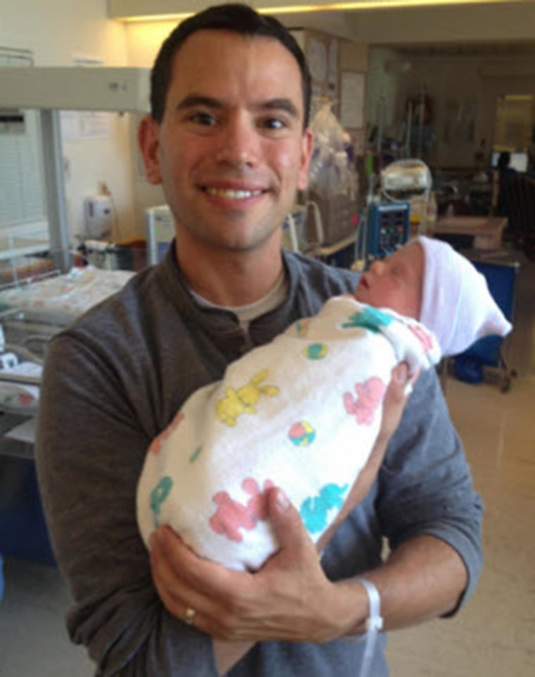 Image: Brian Lande holds his baby, who was born while his wife was in a coma.