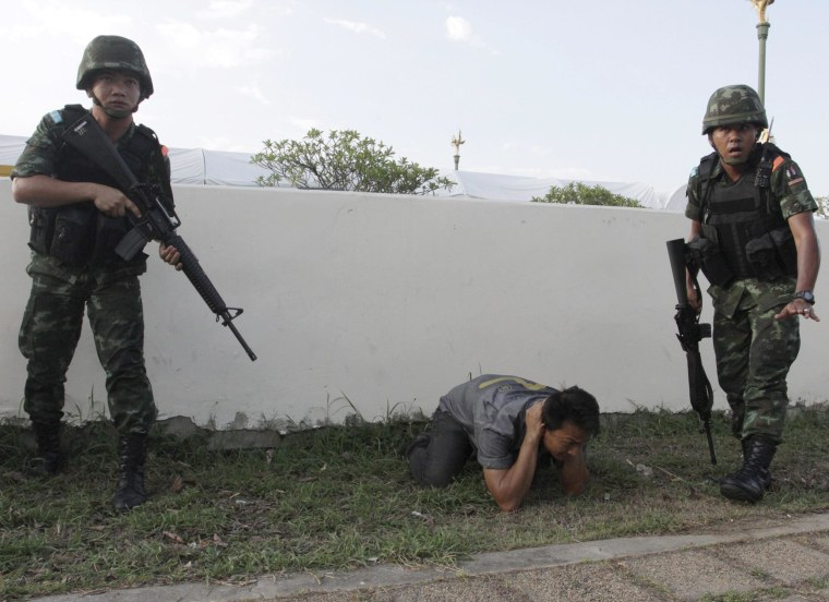 Image: A Thai Red Shirt pro-government supporter is arrested by soldiers after the army declared a coup
