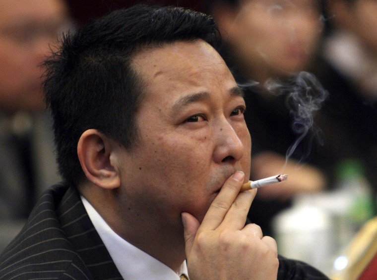 Image: File photo of Liu Han, former chairman of Hanlong Mining, smoking a cigarette during a conference in Mianyang