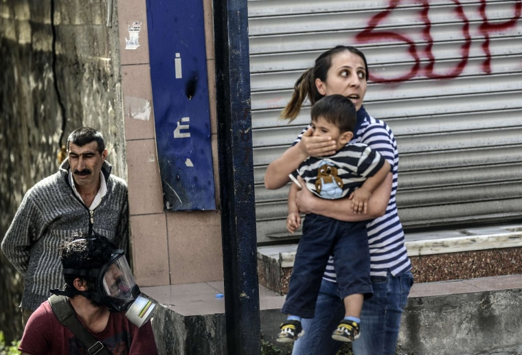 Image: A woman holds her child during clashes in Istnbul