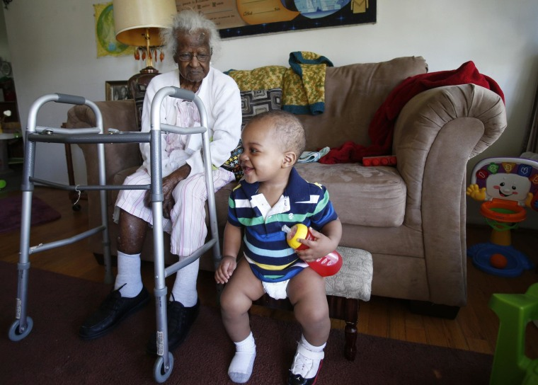 Image: Talley watches her 14-month-old great-great-grandson Armmell Holloway plays next to her during her 115th birthday in her home in Inkster