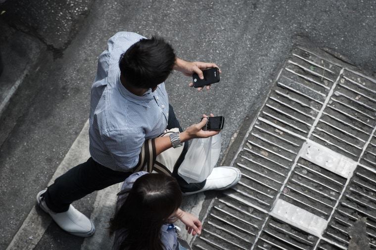 Image: A man holding two smartphones while walking in a street