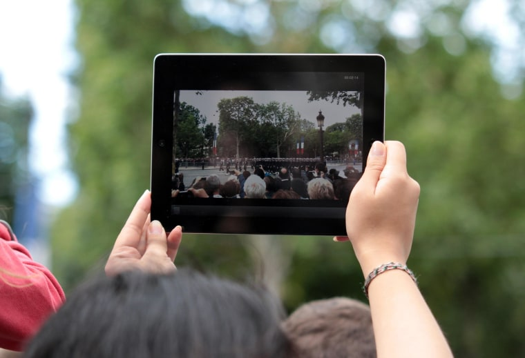 Image: A woman takes a picture with an iPad