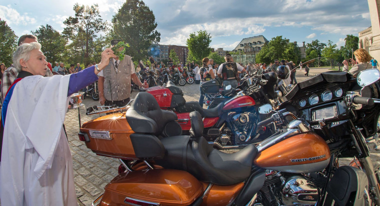 Image: The Rev. Canon Gina Gilland Campbel, left,  sprinkles Holy Water on a Harley-Davidson motorcycle during the Blessing of the Bikes at the Washington National Cathedral