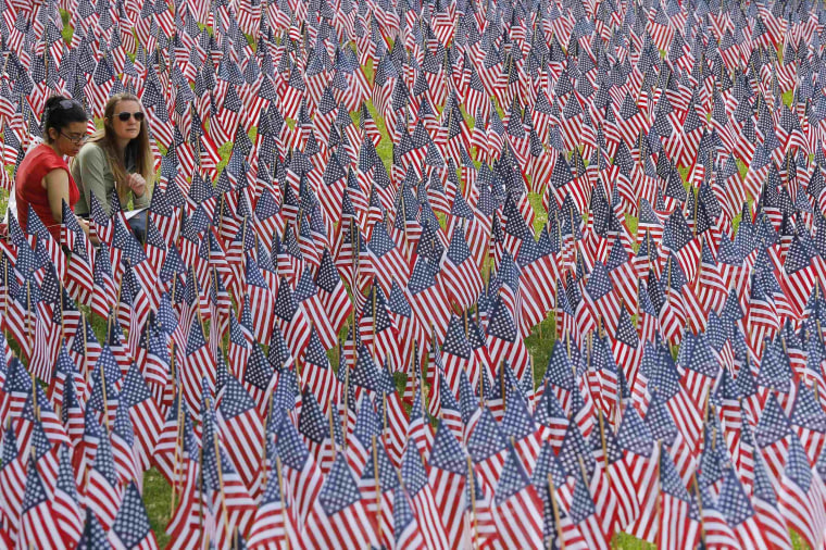 Image: Two women sit at the edge of the field of United States flags displayed by the Massachusetts Military Heroes Fund on the Boston Common in Boston