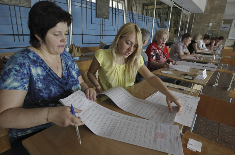 Image: Members of Ukraine's Election Commission prepare for voters