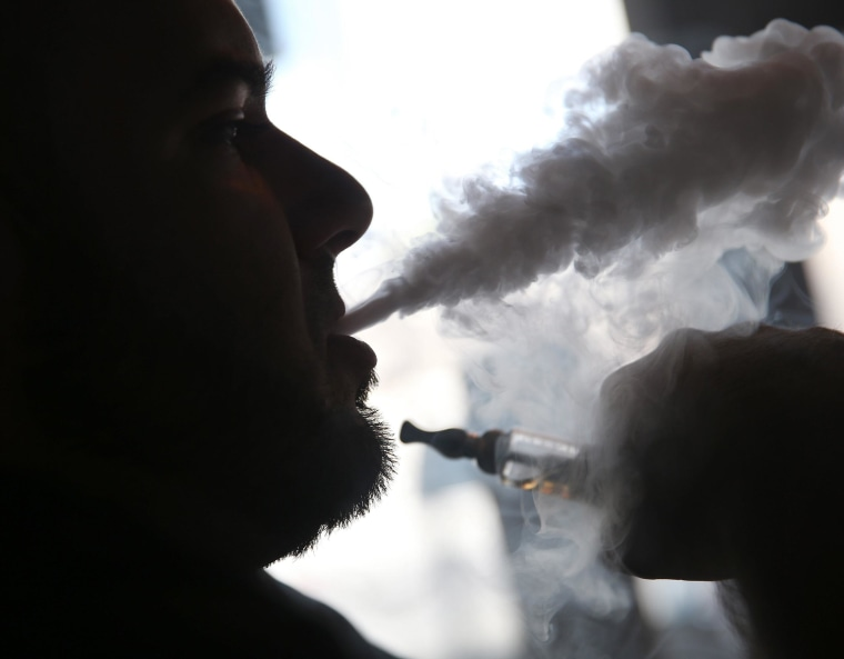 Image: Michael Crespo, a salesman, waits for customers as he enjoys an electronic cigarette in Miami